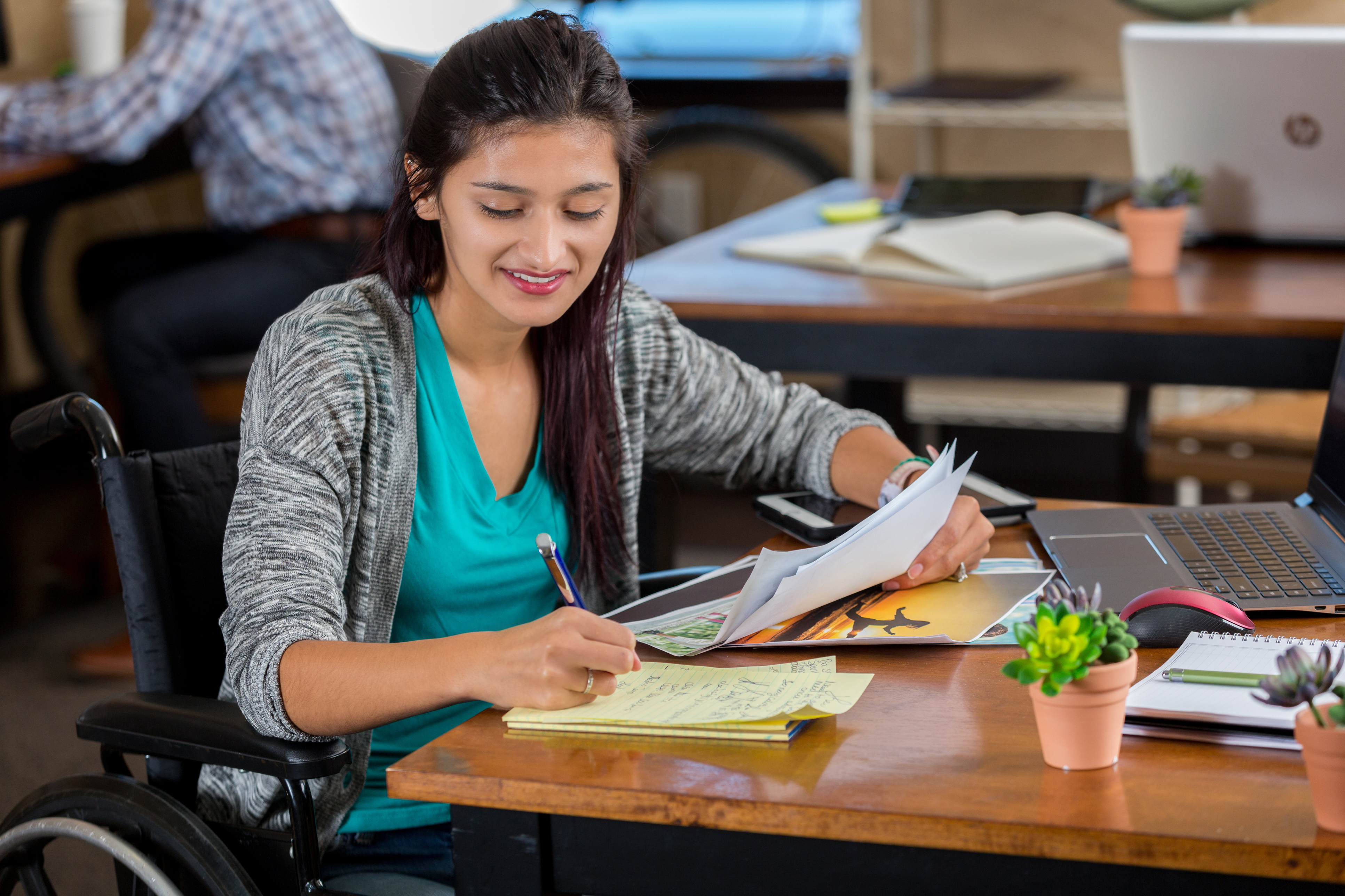 Photo illustrant une étudiante en fauteuil roulant travaillant à la rédaction d'un document.